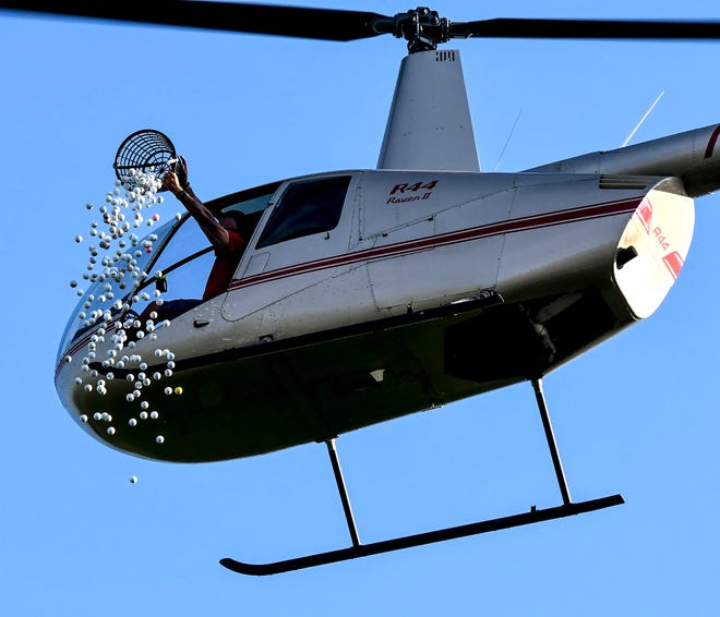 A basket of numbered golf balls are dropped from a helicopter toward a pin placed below on the ground Monday at Buffalo Dunes Golf Course during the Southwest Kansas Pro-Am's LifeSave Transport Ball Drop.  The event, brought back after a few years absence, was an added fundraiser for St. Catherine Hospital's Newborn Intensive Care Unit. The golf balls were purchased by community members, with the closest to the pin winning a cash prize.  This year's winner donated the $3,000 back to the NBICU.  The golf tournament and other events continue through Saturday at both Buffalo Dunes and The Golf Club at Southwind.