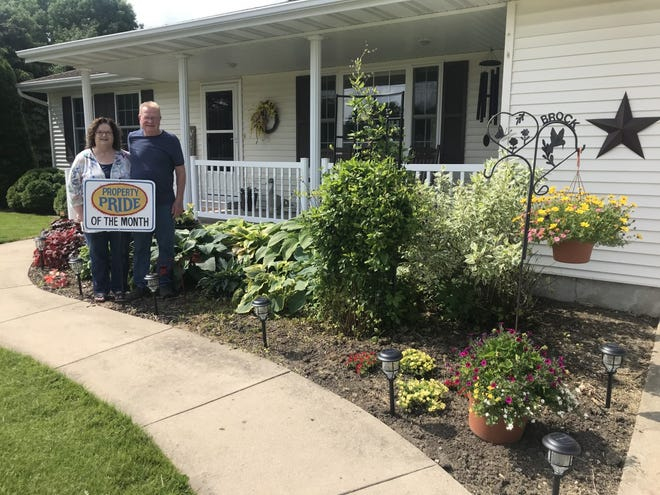 """Pictured are Tom and Sandy Brock who received the June Property Pride. The couple live at 915 NW 6th Street. They  have lived in the home about 3 years.  The couple said, """"Sandy designs and Tom digs.""""  They have 3 grown children and 5 grandchildren."""