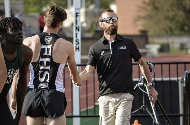 Jason McCullough, right, head track and field coach at Fort Hays State University, congratulates Tiger runner Ethan Lang after a race this season.