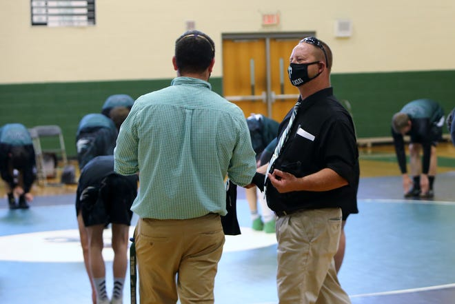 East Henderson coach Doug Lanning, right, talks with his assistant prior to a match against Pisgah earlier this season at East.