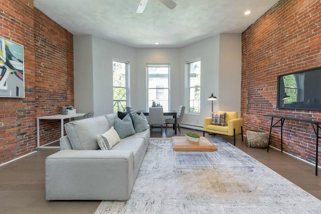 Exposed brick, high ceilings and sunny bay windows give this home charm. Place the dining table in the bay to enjoy treetop views.