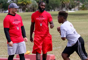 Chris Rainey helps run drills at the Victory Christian football camp on Saturday. The former Lakeland Dreadnaught will report to the B.C. Lions next month.