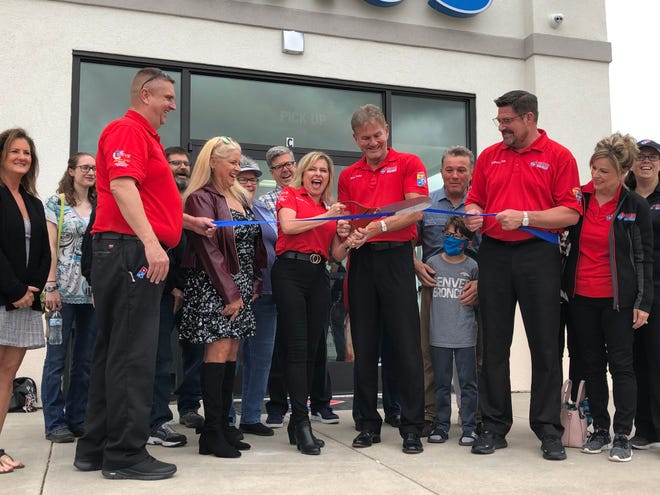 Michelle Bailey cuts the ribbon at the Domino's Pizza Grand Opening on Memorial Day. La Junta's new pizza chain is located at 1 Conley Road.