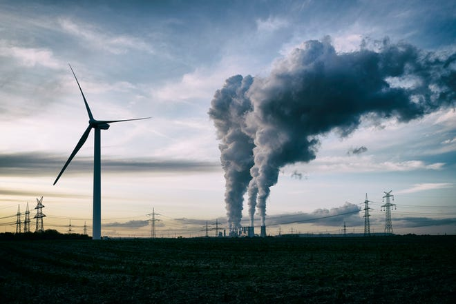 Single wind turbine, a coal burning power plant with pollution and electricity pylons in the background.