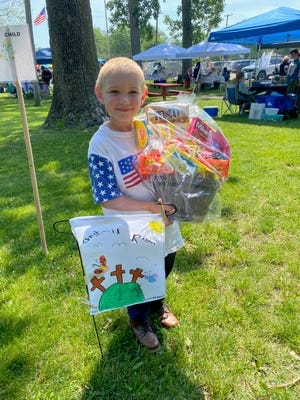 Ebon Woelmer, 7, won a gift basket for placing first among children in a flag-decorating contest held at the Carleton Farmers Market Saturday in Ash-Carleton Park. He was one of 30 people to enter the contest.