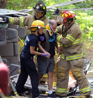 The driver of a vehicle that crashed into a utility pole and rolled over on newly paved Marshall Road in Holliston is rescued by Holliston firefighters, June 8, 2021.