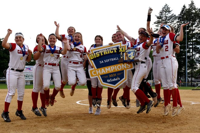 Pocono Mountain East softball players jump with joy and their District 11 Class 5A trophy and banner after defeating Bangor in the district title game in Allentown on Tuesday, June 1, 2021.