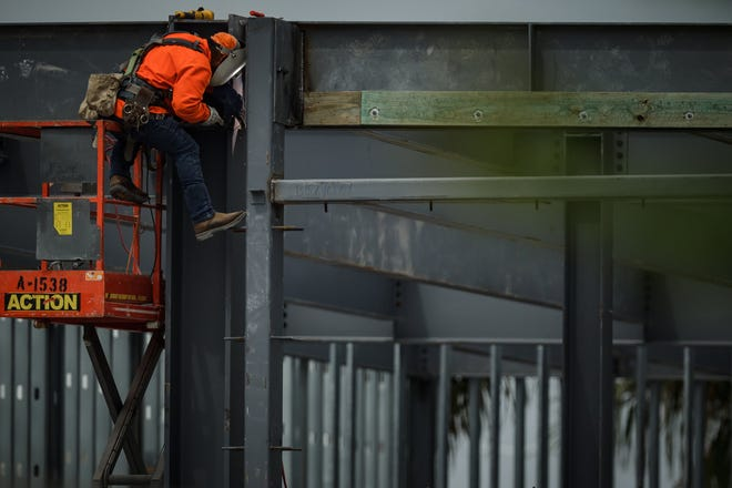 An ironworker welds structural beams together at the future site of a Lazy Dog restaurant in the Uptown Boca retail and apartment development in unincorporated Palm Beach County, Fla. on Wednesday, April 21, 2021.