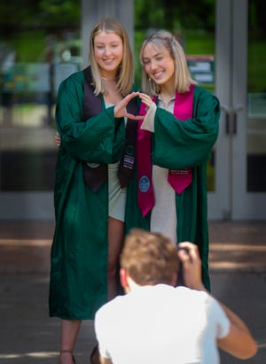 University of Oregon graduates Aubrey Timmons, left, and Emily Scarvie pose for a graduation photo for photographer Julian Croman in front of the Lillis Business School Complex on the UO campus as the end of the school year approaches.