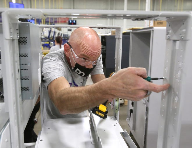 Diebold Nixdorf employee Randy Lowther assembles an automatic teller machine at the company's production center in North Canton's Hoover District. The facility is being expanded to create additional warehouse space, as well as offices for engineers and researchers.