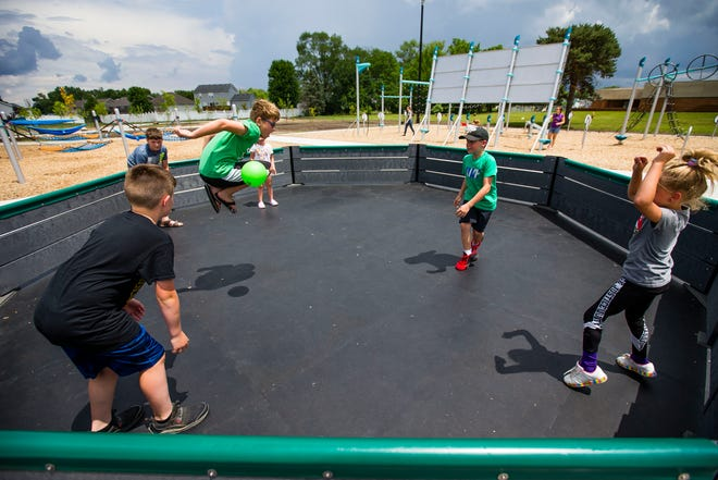 Brayden Rose, 10, tries to jump away from a shot, while playing with Brody Cota, 11, bottom left, Gavin Lochotzki, 12, top, from left, Michelle Nicholas, 6, Landon Dean, 9, and Mae-Ella Lochotzki, 7 during a game of Gaga Ball Tuesday, June 8, 2021 at Hero's Park in Mishawaka.