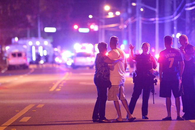 Police officers in Orlando, Florida, direct family members away from a fatal shooting at the Pulse nightclub in Orlando on June 12, 2016. A gunman opened fire in the club, leaving 49 people dead and 53 wounded.