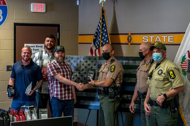 Justin Raver, flanked by Revolution Coffee co-owners Tony Segura and Scott Packee, deliver coffee to Illinois State Police Dist. 7 troopers last week.