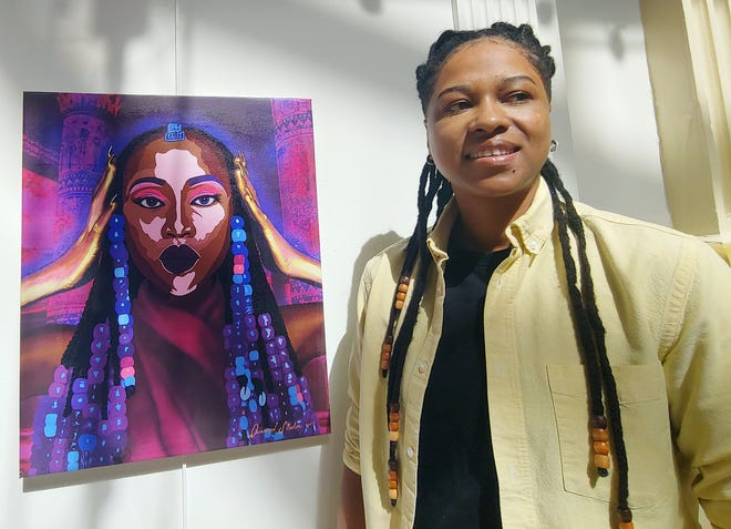 Artist Diamond Campbell with one of her featured works at the Bank of the Arts Juneteenth exhibit.