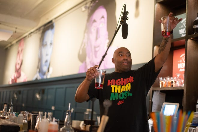 Ty Platt, a bartender at Brew Bank, holds up examples of properly portioned pours of spirits during the restaurant's mixology class in May.