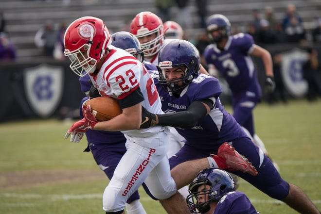 St. Johns Ethan Shibley runs the ball as he is tackled by St. Peter-Marian's Marcos Perez-Burgos during the 95th annual Thanksgiving game in 2019.