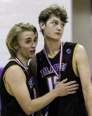 Olentangy's Sam Irwin (left) tries to console teammate Jacob Nussdorfer as they watch Middletown Fenwick receive the Division II state championship trophy June 6 at Pickerington Central. The Braves lost the state final 25-22, 25-18, 25-16.