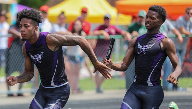 Africentric's Justin Fudge hands the baton to Deangelo Fuller during the 400 relay in the Division III state meet June 5 at Westerville North. The Nubians finished eighth in the event, but they won the 800 relay and Fudge captured the title in the long jump.