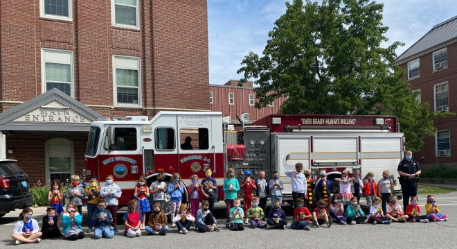 West Newbury Police Officer Michael Dwyer and Page School first-grade students pose after making their donations to the Council on Aging Food Pantry.