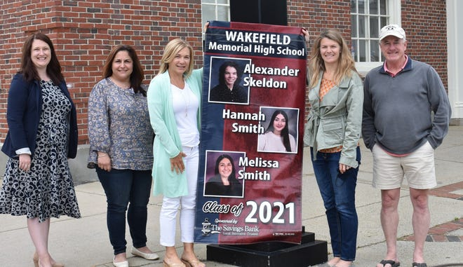 Raichelle Kallery, center, executive vice president, senior retail banking officer at The Savings Bank, joined bank staff and representatives of the Wakefield Memorial High School Senior Night Committee as the banners honoring the Class of 2021 were placed on light poles along Main Street. Sponsored by The Savings Bank, the banners feature the name and picture of each graduate. On hand for the unveiling of the banners were, from left: The Savings Bank Marketing Coordinator Ally Houghton, Marie Smith of the bank's mortgage department whose daughter is featured on the banner, Kallery, Senior Night Committee Secretary Catherine Dhingra and Senior Night Development Director Mike Boudreau.