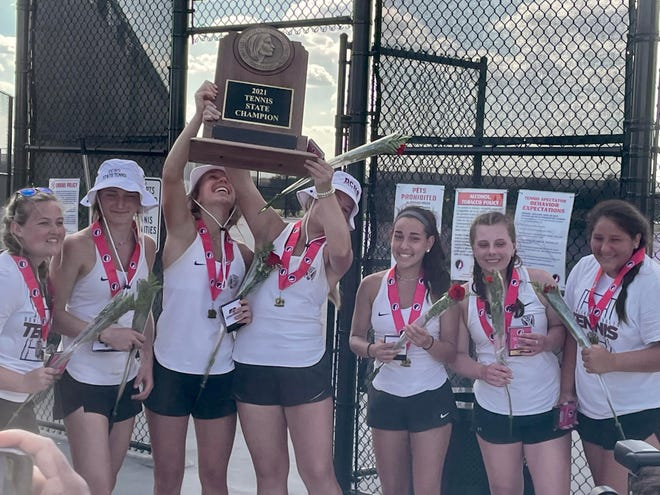 The Dowling Catholic girls celebrate with the state tennis championship trophy on Saturday, June 5, 2021.