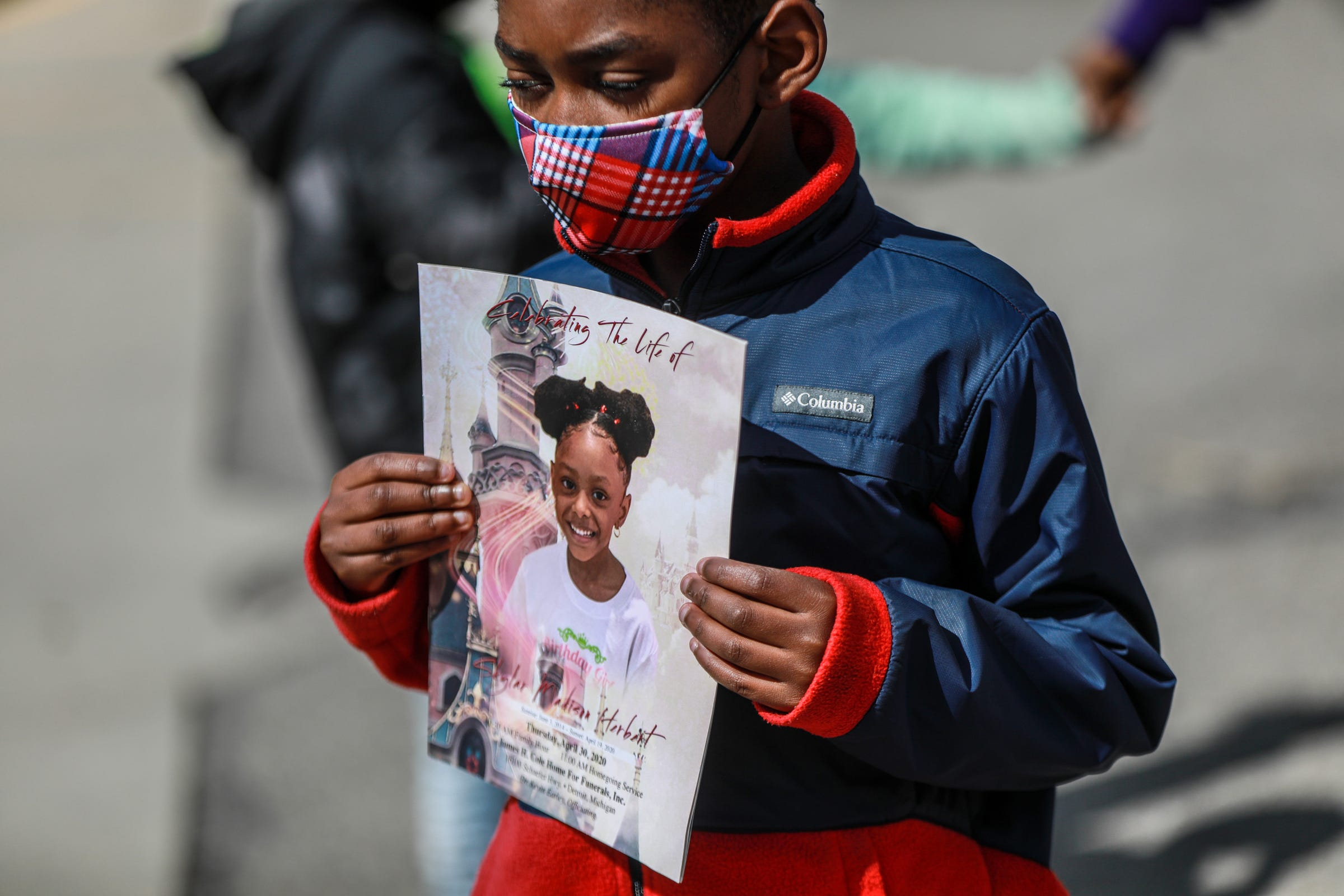 James Foster, 7, of Detroit holds the memorial service program for his classmate, Skylar Herbert, who was initially Michigan's youngest COVID-19 victim, at a memoriam for Skylar at their elementary school,  University Prep Academy - Mark Murray Campus, on May 8, 2021. Foster quietly said Skylar was his best friend.