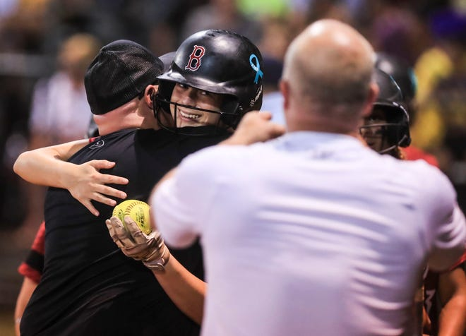 After hitting a three-run homer at her first at bat, senior Sydney Martin gets the ball as well as a hugs by the Ballard coaching staff in the Seventh Region final Monday evening. It was especially emotional to the team as Martin, a senior and outfielder, had attended the funeral of her mother Ashley Ryan earlier in the day before the game. Her mother died June 2 at 48. June 7, 2021
