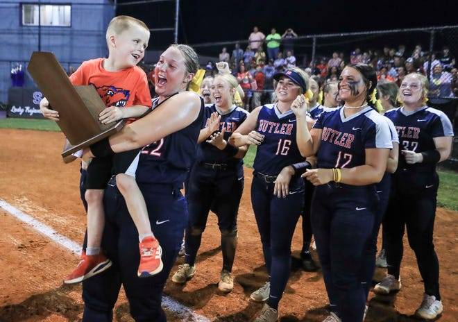 Butler's Emily Williams picks up Blake Braun, the son of the Butler softball coach Brittany Braun, as he carries the championship trophy after the Bearettes beat Bullitt East 8-0 in the Sixth Region final Monday evening.  June 7, 2021