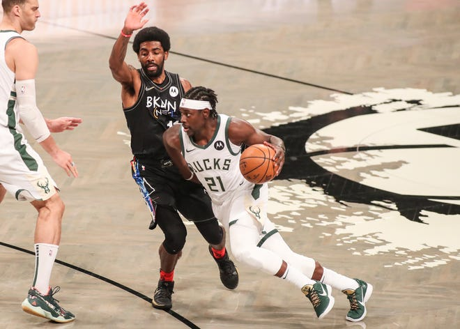 Jun 7, 2021; Brooklyn, New York, USA; Milwaukee Bucks guard Jrue Holiday (21) drives past Brooklyn Nets guard Kyrie Irving (11) in the first quarter during game two in the second round of the 2021 NBA Playoffs. at Barclays Center. Mandatory Credit: Wendell Cruz-USA TODAY Sports