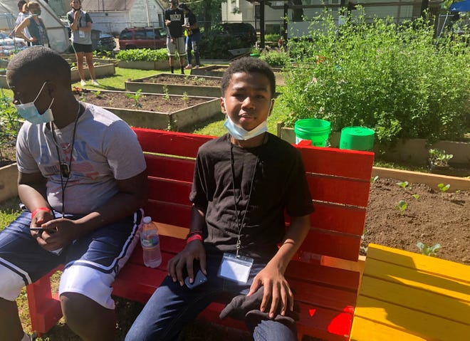 Izaiah Cole, 14, takes a break after cleaning up several blocks near the We Got This urban garden with columnist James E. Causey. Izaiah is one of 40 boys who will work at the garden on the corner of N. 9th and W. Ring streets this summer. Boys working in the garden will earn $40 for four hours of work each week and also gain valuable mentoring from men in the community.
