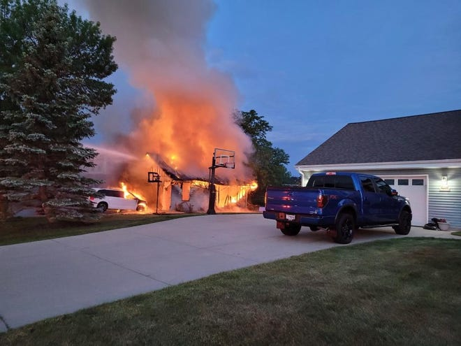 A water stream, left, from a Germantown Fire Department engine is directed at a fire in a house in the village early Tuesday morning. The family that owns the house was able to evacuate safely.