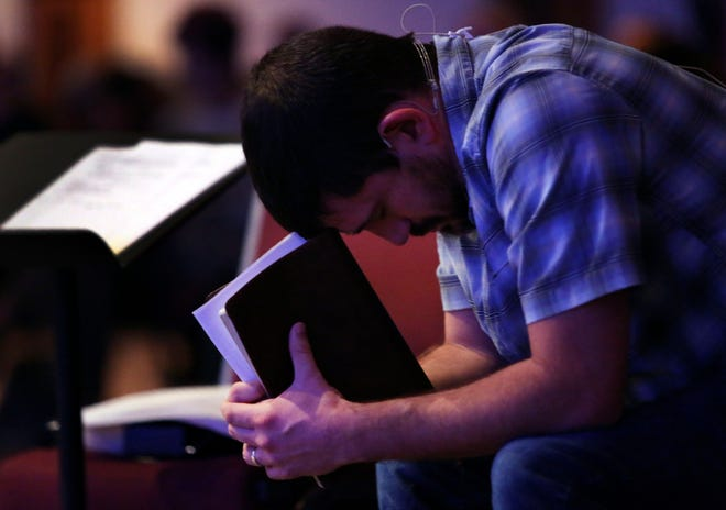 Pastor Mike Leake, of Calvary of Neosho, a Southern Baptist church, rests his head on his Bible as he prays during service in Neosho, Mo., on Sunday, Nov. 22, 2020. (AP Photo/Jessie Wardarski)