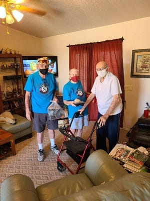 At left, volunteers Rob and Ruth Ann Glover deliver a Deming Senior Center meal to a client. Home delivered meals have increased from 130 to 230 since the pandemic.