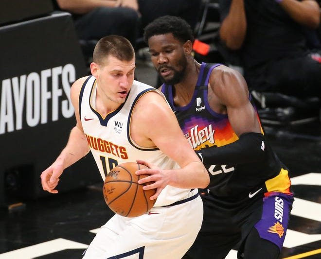 Denver Nuggets center Nikola Jokic (15) is defended by Phoenix Suns center Deandre Ayton (22) during the first quarter of the NBA second round playoff series in Phoenix. June 7, 2021.