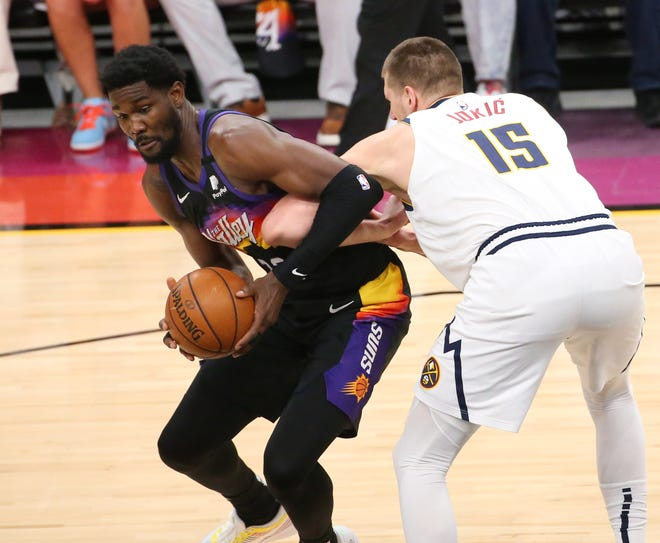 Phoenix Suns center Deandre Ayton (22) is defended by Denver Nuggets center Nikola Jokic (15) during the first quarter of the NBA second round playoff series in Phoenix. June 7, 2021.