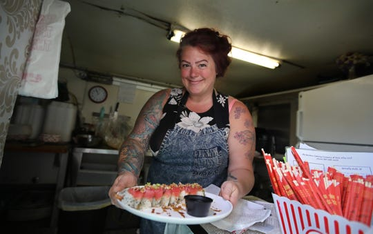 Kimberly Roth, owner and chef, serves up a GoGo sushi roll from her Back Alley Grill food trailer in Sodus Point Friday, June 4, 2021.