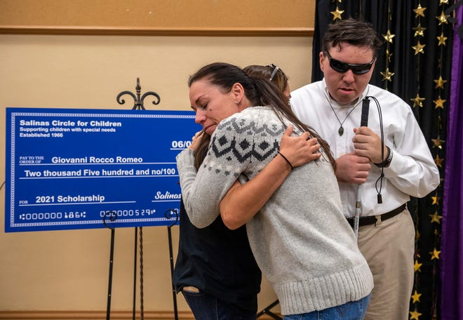 Sascha Grant, hugs her son's longtime teacher during Giovanni Rocco Romeo's award ceremony inside the Monterey County Office of Education in Salinas, Calif., on Monday, June 7, 2021.