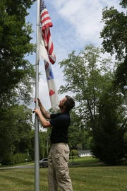 David Pinder raises the American Flag in the Iron Hill area. Pinder started a program at Comcast that replaces worn, faded or tattered flags.
