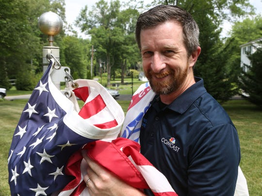 David Pinder replaces a flag in the Iron Hill area. Pinder started the Veterans Network Flag Replacement Program at Comcast which replaces worn, faded or tattered flags.