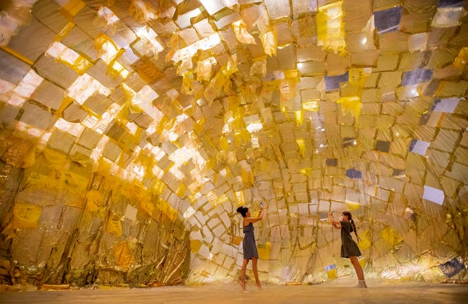"""Nicole Flowers and her 8-year-old daughter, June, explore the art installation """"Into the Breath"""" by Stefano Ogliari Badessi at Wonderspaces Austin on Tuesday, June 8, 2021.  The Chinese dragon made of teabags is one of four new installations in the 28,000-square-foot interactive art exhibit that opened last summer. Wonderspaces features art installations that rotate regularly from world-renowned artists."""