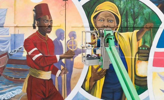 An artist works on the mural commemorating Juneteenth in Galveston. The mural includes Esteban de Dorantes and Harriet Tubman. Viewers will be able to use their smartphones to learn more about the people depicted in the mural.