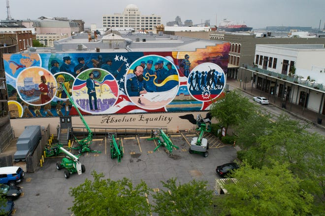 Artists work on final details of a 5,000-square-foot mural on the former Osterman Building in Galveston. The mural will be dedicated Saturday as part of Juneteenth celebrations.