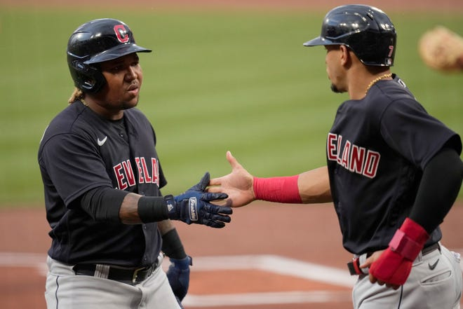 Cleveland second baseman Cesar Hernandez, right, is congratulated by teammate Jose Ramirez after scoring during the first inning of a 10-1 win over the St. Louis Cardinals on Tuesday night. [Jeff Roberson/Associated Press]