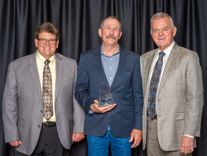 CLA President Dwain Weinrich and CLA executive Bill Hammerich present the Top Choice award for industry service to retired Colorado State Veterinarian Keith Rohr during CLA's annual convention.
