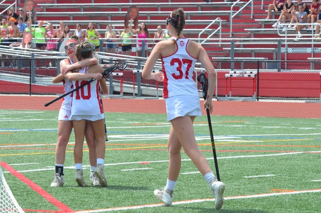Rancocas Valley senior wraps Reese DeMarco in a hug as Ella Ruminski rushes over to celebrate DeMarco's goal