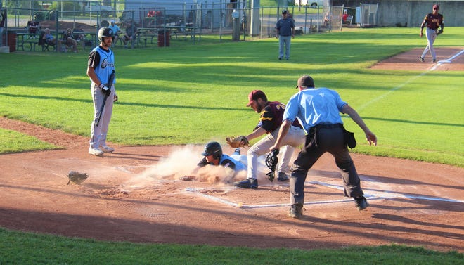 Cale Blasi slides underneath the tag at home plate for the first run of the game for the Cannons.