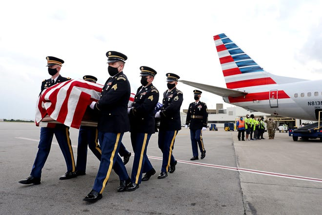 An Ohio Army National Guard Honor Guard carries a casket containing the remains of Army Pfc. James Wilmer White, which arrived Tuesday night at John Glenn Columbus International Airport. White was killed in action during World War II, and a funeral is scheduled for Saturday in Meigs County,