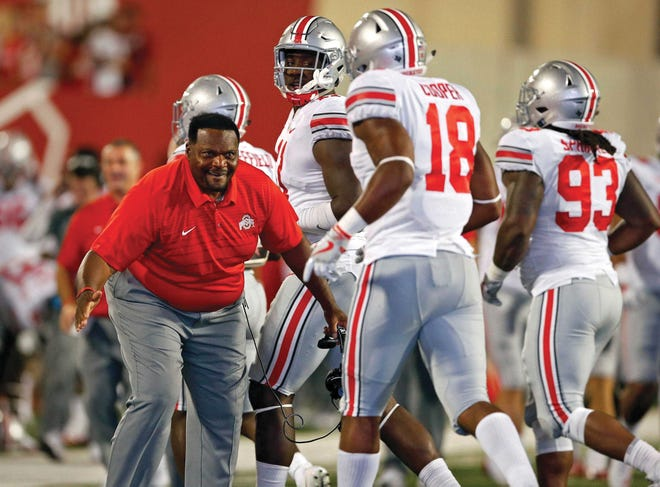Larry Johnson welcomes Jonathon Cooper to the sideline in a 2017 game, with Jalyn Holmes looking on.