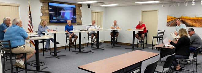 The scene from Tuesday evening's special CHEDA Board meeting at Valley Technology Park, with CHEDA legal counsel Olivia Leyrer, seated right foreground, providing some comments. Counter-clockwise from Leyrer are city council member Joe Kresl, CHEDA Executive Director Craig Hoiseth, CHEDA Board members Leon Kremeier, Steve Erickson (also a city council member), Paul Eickhof, Kurt Heldstab, Betty Arvidson, Craig Buness, and council member/CHEDA liaison Wayne Melbye. On the TV screen is CHEDA Board member and city council member Tom Vedbraaten, participating remotely from Florida.