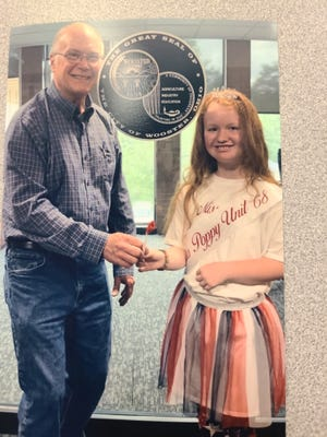 Rylee McCullough, 2021 Miss Poppy from the American Legion Auxiliary Unit 68, presents Wooster Mayor Bob Breneman with a poppy in remembrance of Memorial Day.